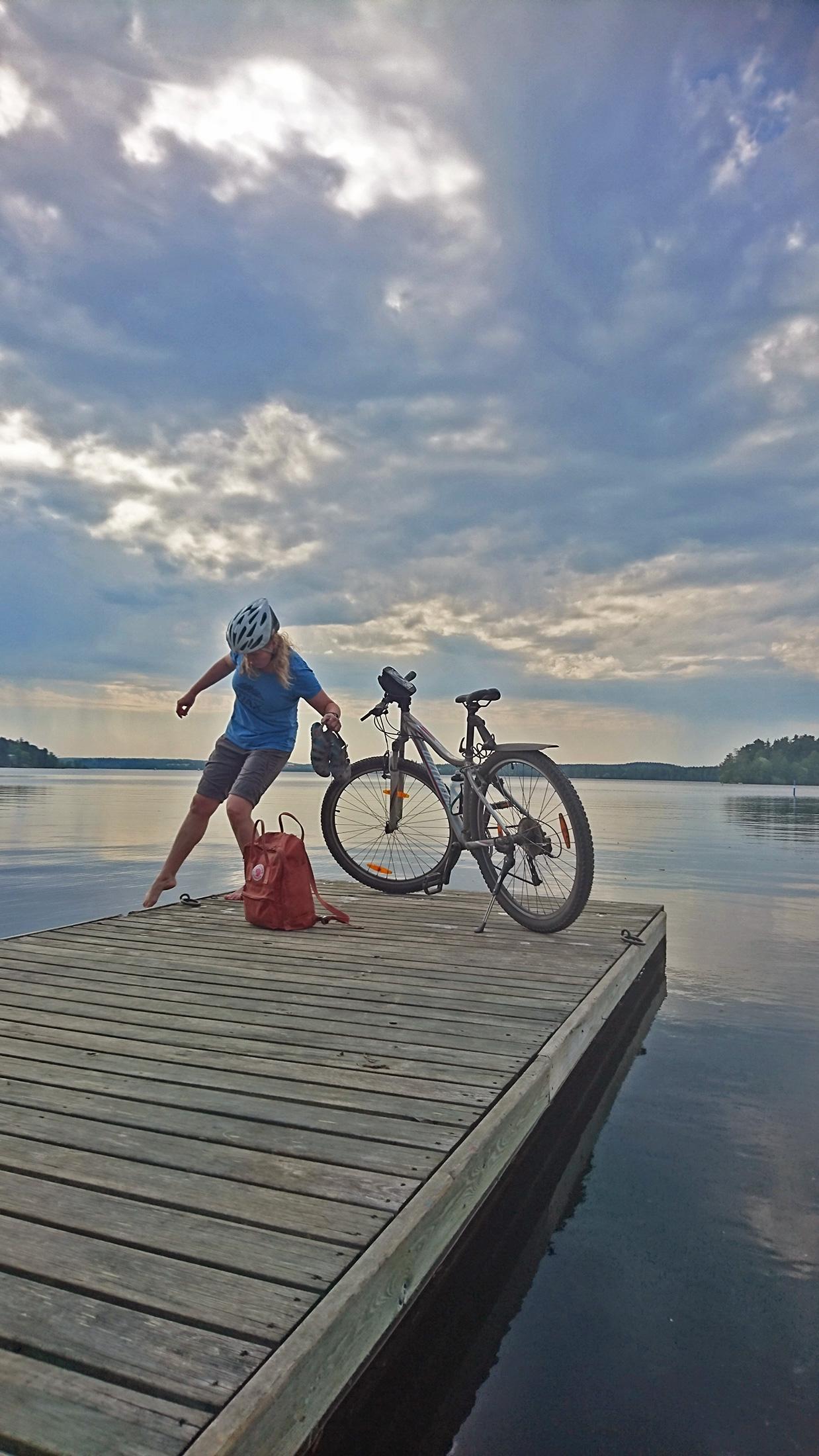 Nainen kastaa varpaitaan veteen laiturilta polkupyörä vieressään.
