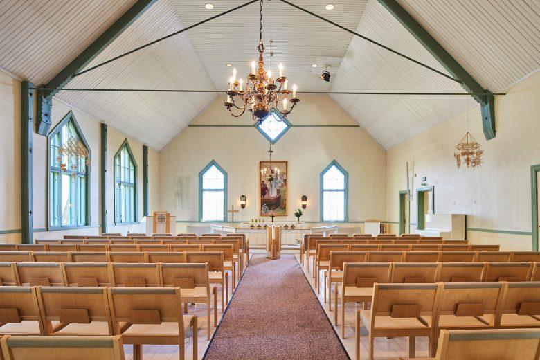Siuron puukirkko on sisältä valoisa ja vaalea. Katosta roikkuu kultainen kattokruunu ja kirkonpenkit ovat puunväriset.