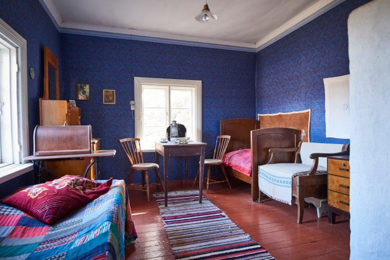 Työläiskotimuseon toisessa huoneessa on siniset seinäpaperit ja kaksi päästä vedettävää sänkyä.