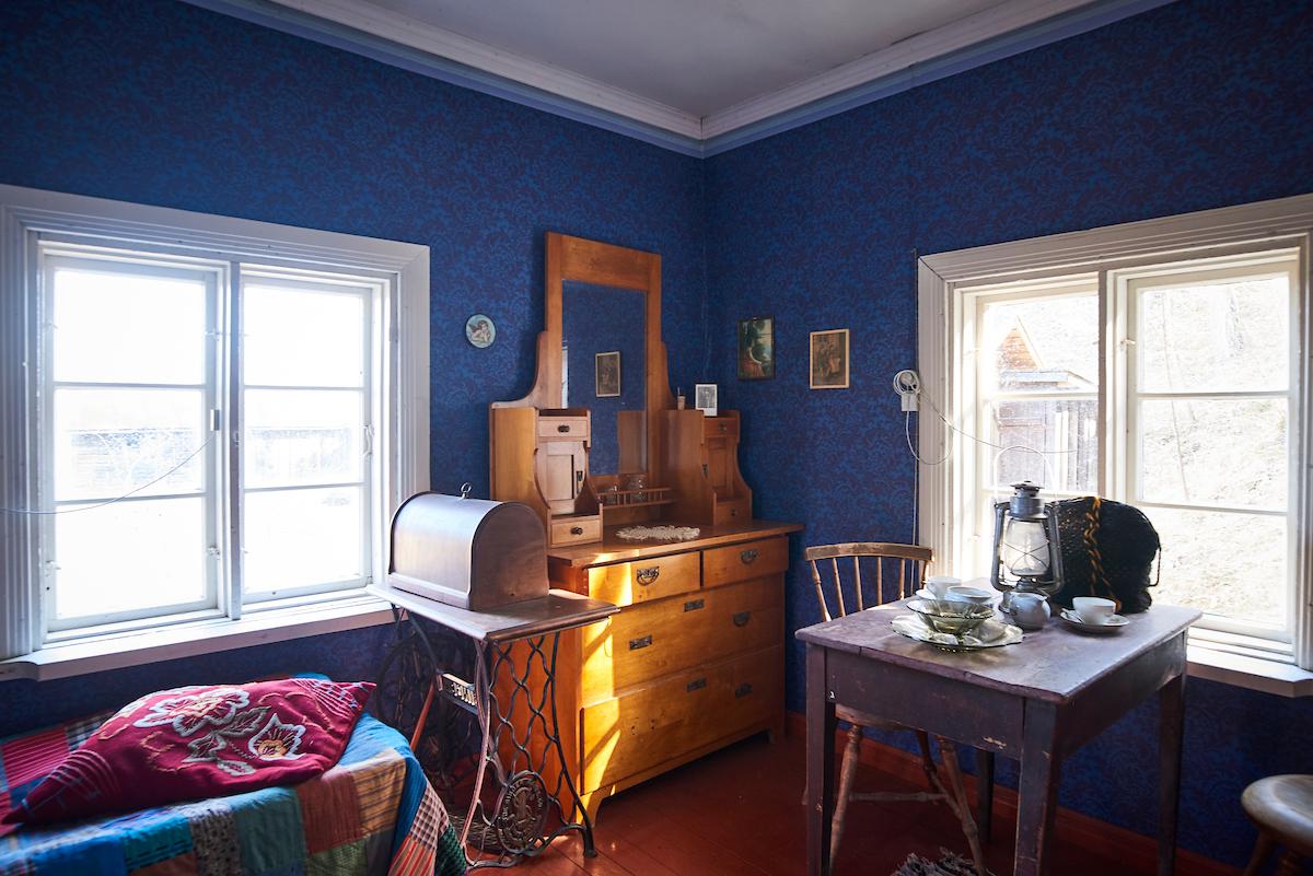 Makuuhuoneen ikkunan edessä on pieni pöytä, jossa on öljylamppu. Seinän vieressä on piironki ja ompelukone.