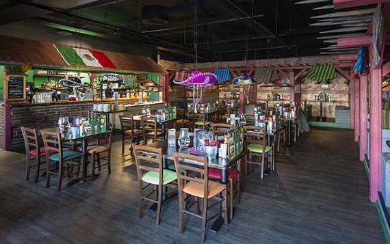 Pancho Villan meksikolaishenkisesti sisustettu ravintolasali, joka on valaistu värikkäillä valoilla.