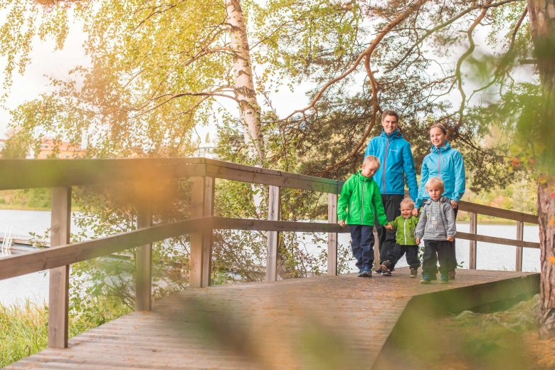 Isä, äiti ja kolme leikki-ikäistä lasta kävelevät aurinkoisena syyspäivänä puusiltaa pitkin Maatialanharjun luontopolulla.