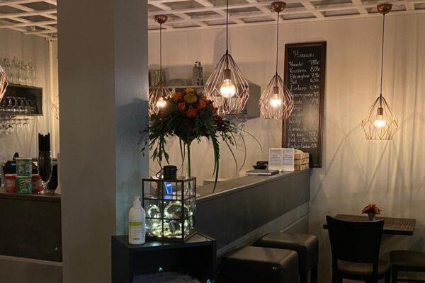 Bistro Minean ravintolasali, jossa baaritiskin yläpuolella roikkuvia tunnelmavalaisimia ja ravintolapöytiä.