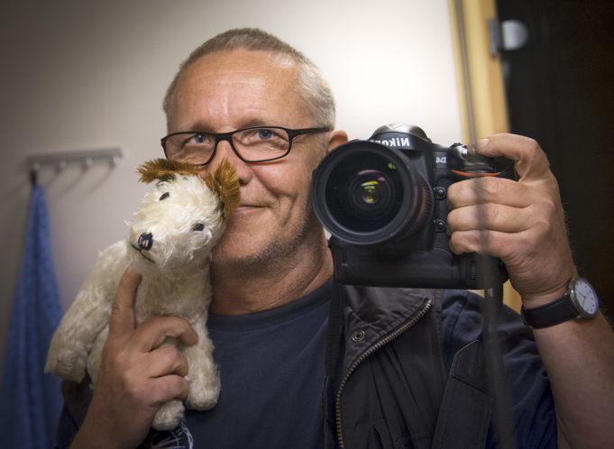 Edesmennyt valokuvaaja Raine Lehtoranta pitää sylissään koirapehmolelua ja ottaa valokuvaa itsestään peilin kautta.