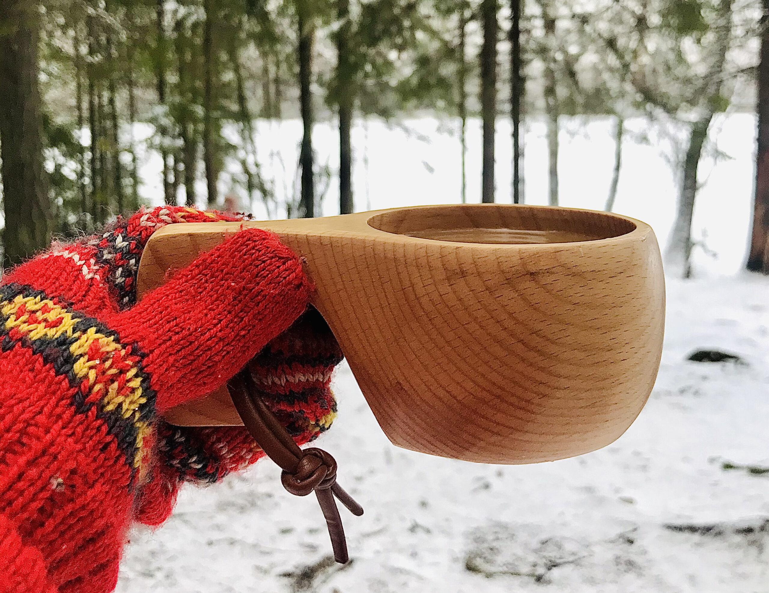 Nainen pitää kahvia täynnä olevaa kuksaa kädessään Ruutanajärven rannalla.