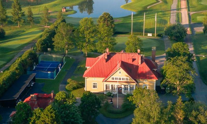 Alastalon keltainen puukartano, jota ympäröivät vihreät Nokian River Golfin golfkentät.
