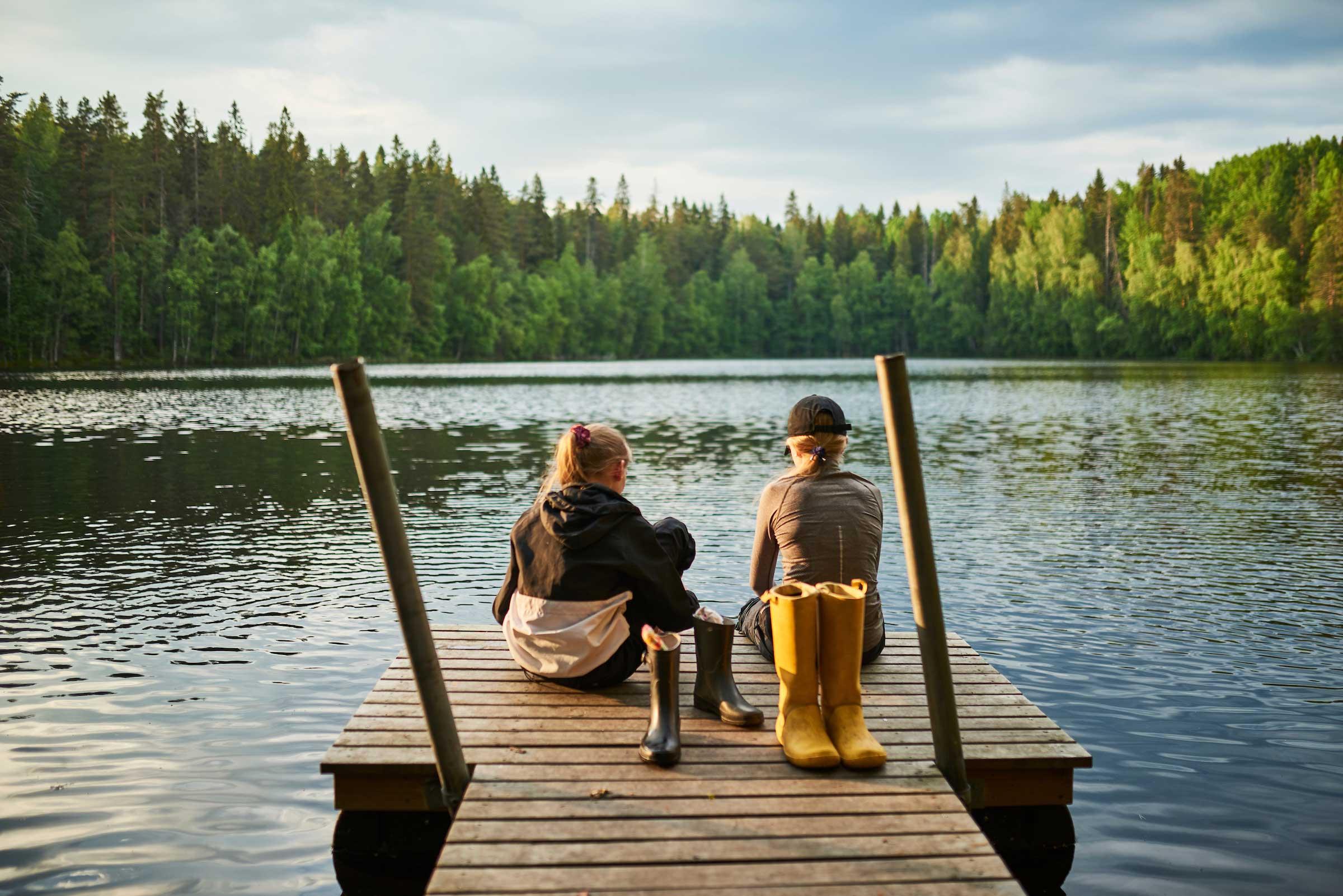 Kaksi teini-ikäistä tyttöä istuu Ruutanajärven laiturilla vieressään kumisaappaat.