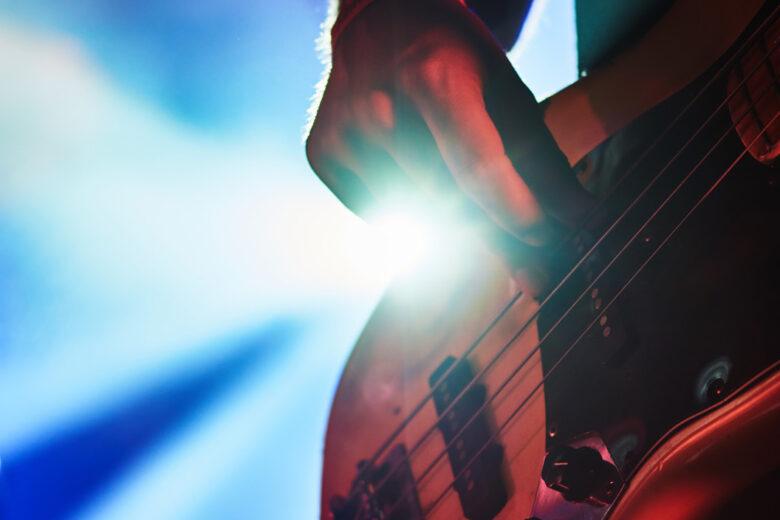 Mies soittaa kitaraa rock-konsertissa.
