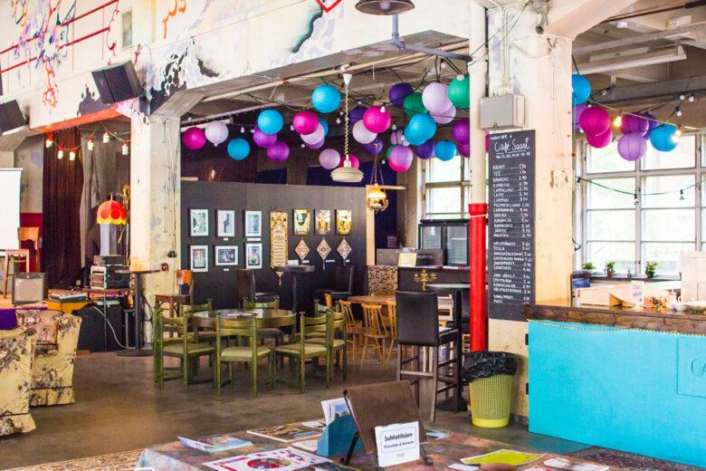 Tehdas 108:n värikkäästi sisustettu ja koristeltu iso sali, jossa on myös Cafe Saari ja kahvilan pöytiä.