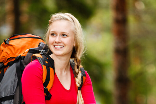 Hymyilevä nainen istuu rinkka selässä ison kiven päällä metsässä.
